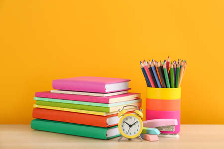 Different school stationery and alarm clock on table against orange background, space for text. Back to school