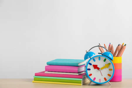 Different school stationery and alarm clock on table against white background, space for text. Back to school Imagens