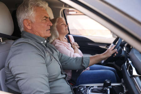 Senior man holding steering wheel while his wife having heart attack in car