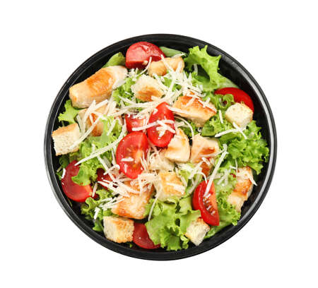 Delicious fresh salad in plastic container on white background, top view