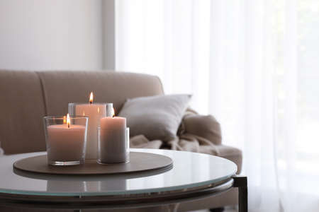 Burning candles in glass holders on table indoors. Space for text