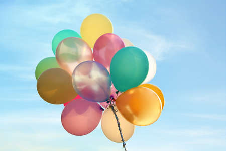 Bunch of bright balloons in blue sky
