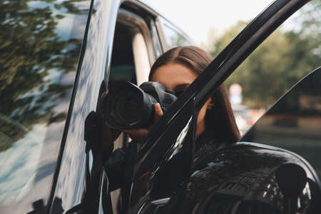 Private detective with camera spying near car outdoors Foto de archivo