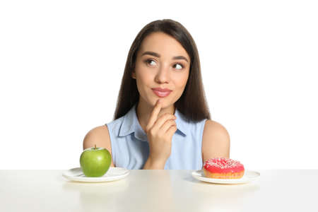 Doubtful woman choosing between apple and donut at table on white background