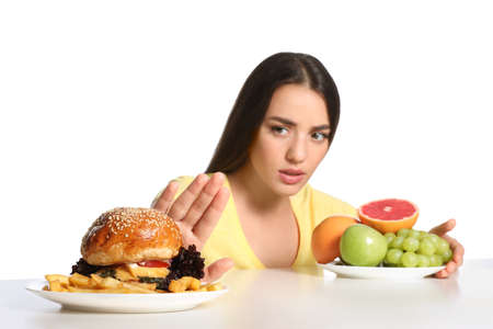 Woman choosing between fruits and burger with French fries on white background
