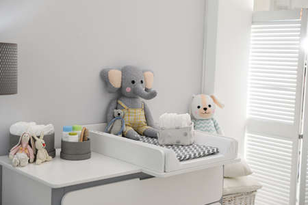Changing tray and pad on chest of drawers in baby room. Interior design