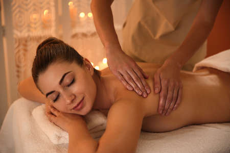 Young woman receiving back massage in spa salon