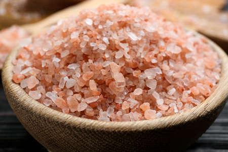 Pink himalayan salt in wooden bowl on table, closeup