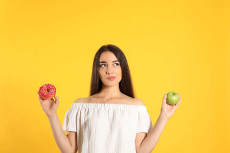 Doubtful woman choosing between apple and donut on yellow background Stockfoto