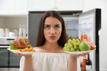 Woman choosing between fruits and burger with French fries near refrigerator in kitchen Stock Photo