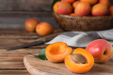 Delicious fresh ripe apricots on wooden table, closeup. Space for text