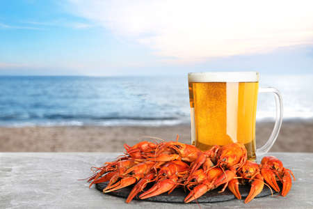 Cooked crayfishes served with beer on gray table near sea