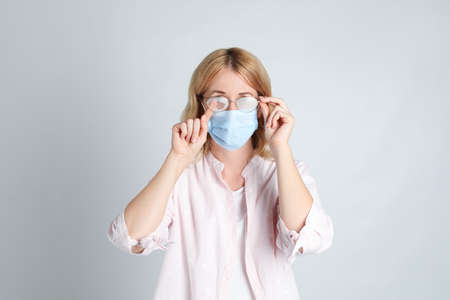Woman wiping foggy glasses caused by wearing medical mask on light background