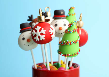 Delicious Christmas themed cake pops on light blue background, closeup