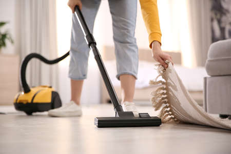 Young woman using vacuum cleaner at home, closeup Reklamní fotografie