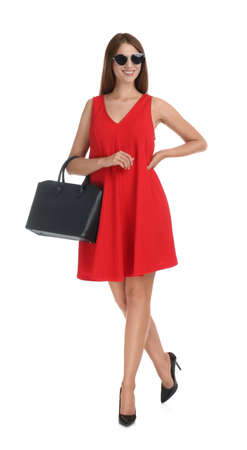 Young woman wearing stylish red dress with elegant bag on white background