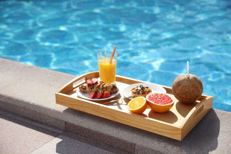 Tray with delicious breakfast near swimming pool