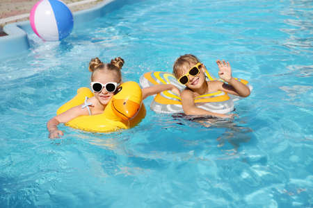 Happy children with inflatable rings in outdoor swimming pool on sunny summer day