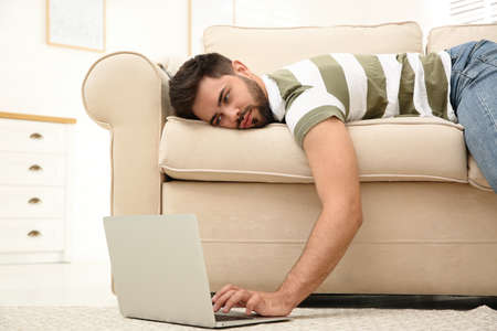 Lazy young man using laptop while lying on sofa at home