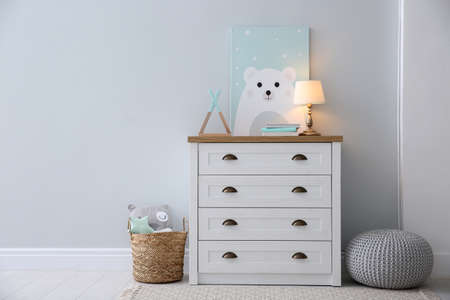 Modern white chest of drawers near light wall in child room, space for text. Interior design