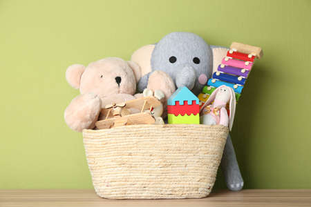 Basket with different toys on wooden table Stock fotó