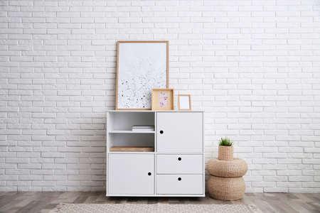 Modern white cabinet near brick wall in room. Interior design
