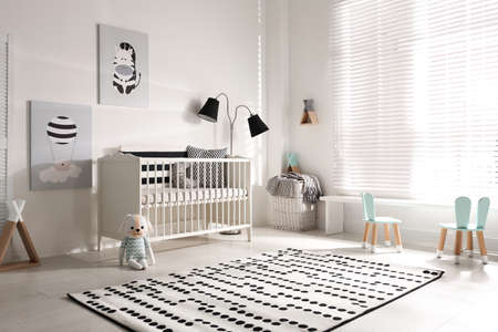 Cute baby room interior with crib and decor elements Stockfoto