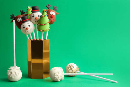 Delicious Christmas themed cake pops on green background Imagens