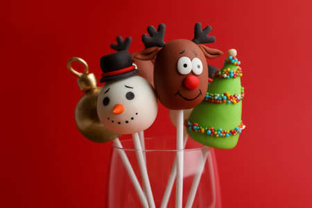 Delicious Christmas themed cake pops on red background, closeup