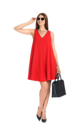 Young woman wearing stylish red dress with elegant bag on white background Stockfoto