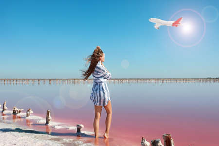 Beautiful woman near pink lake and airplane in sky on background. Summer vacation Banque d'images