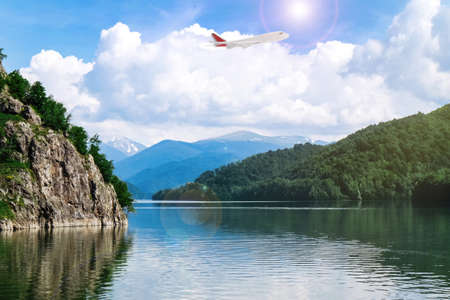 Airplane flying over beautiful lake surrounded by mountains on sunny day