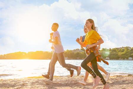 School holidays. Group of happy children running on beach