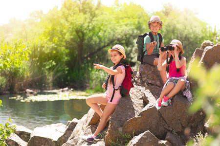 School holidays. Group of happy children sitting on rocks near river