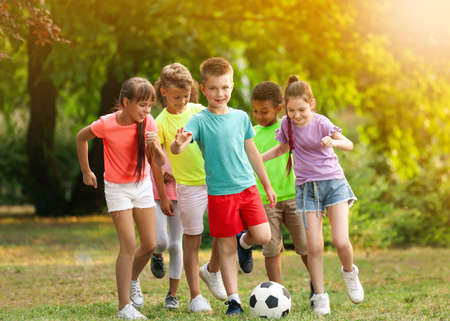 School holidays. Group of happy children playing football outdoors Stock fotó