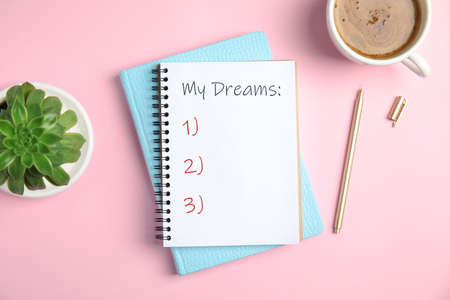 Notebook with dreams list on pink table, flat lay