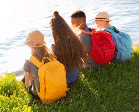 School holidays. Group of children sitting on green grass near river