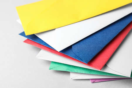 Colorful paper envelopes on light background, closeup