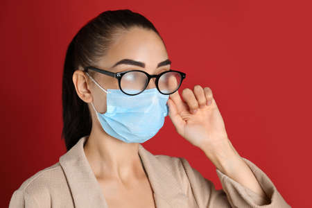 Woman wiping foggy glasses caused by wearing medical mask on red background
