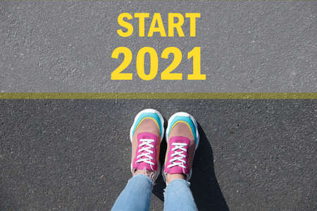 Text Start 2021 on asphalt in front of woman, top view Imagens