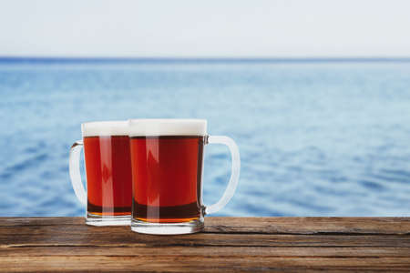 Glass mugs of delicious kvass on wooden table near sea. Space for text