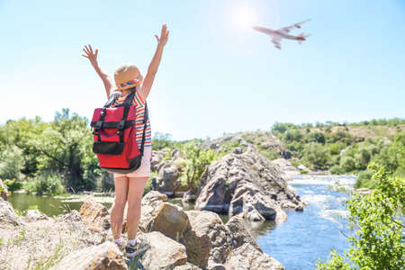 Little girl near river and airplane in sky. Summer vacation