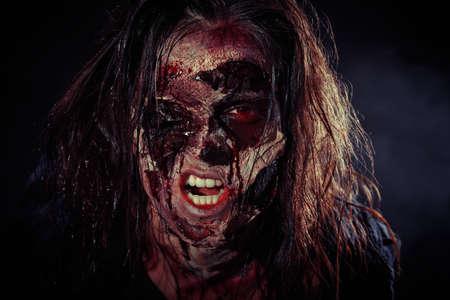 Scary zombie on dark background, closeup. Halloween monster Foto de archivo