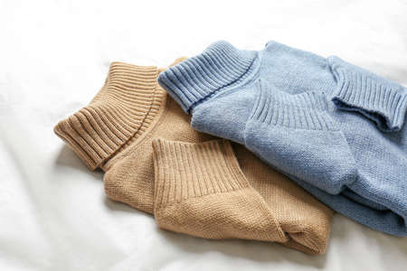 Stylish soft knitted sweaters on white fabric