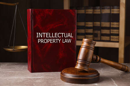 Intellectual Property law book and judge's gavel on gray marble table