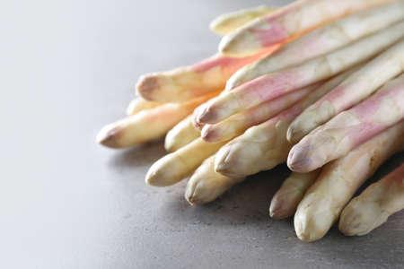 Pile of fresh white asparagus on gray table, closeup