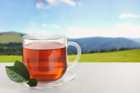 Glass cup of fresh hot tea on wooden table against blurred mountain landscape. Space for text