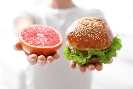 Concept of choice. Woman holding grapefruit and burger on white background, closeup Stock Photo
