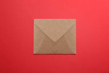 Brown paper envelope on red background, top view