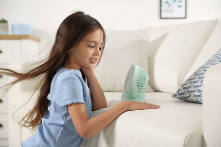 Little girl enjoying air flow from portable fan at home. Summer heat